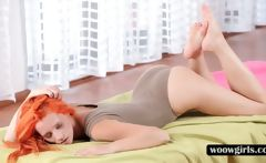 Stunning redhead spreading legs in tight body suit