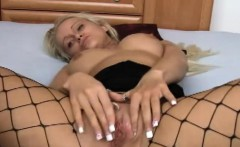 Hot blonde Nicole is lying on a bed wearing fishnet
